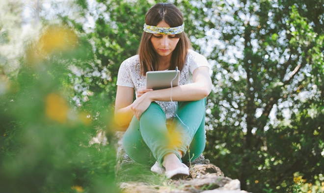 Young woman listening music and reading with digital tablet on a